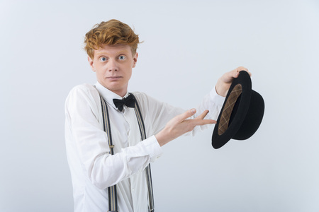 Portrait of young man showing magic with hat LANG_EVOIMAGES