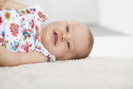 Germany,North Rhine Westphalia,Cologne,Baby girl lying on carpet,smiling