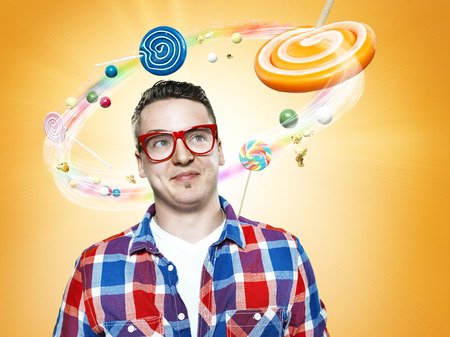 Smiling young man looking at flying candies,Composite