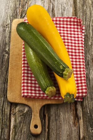 Green and yellow courgettes with napkin on chopping board,close up