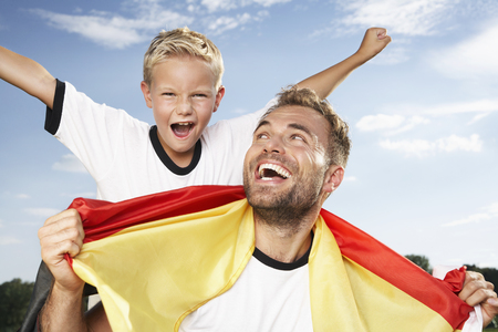 Germany,Cologne,Father and son cheering in football outfit