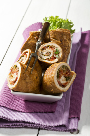 Tray of pork roulades with napkin on wooden table,close up