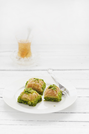 Plate of turkish baklava and glass of tea on wooden table,close up LANG_EVOIMAGES