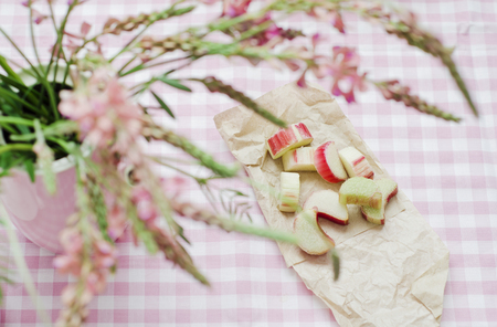 Rhubarb pieces with pink flowers on table,close up