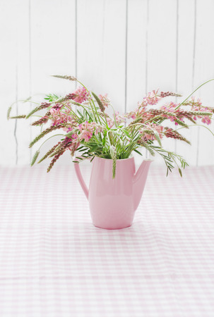 Bunch of pink flowers in can on table,close up LANG_EVOIMAGES