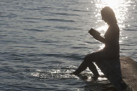 Germany,Bavaria,Mature woman reading book at Lake Stamberg