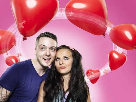 Couple looking at heart-shaped balloons,Composite LANG_EVOIMAGES