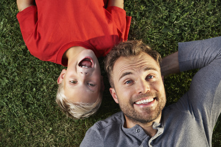 Germany,Cologne,Father and son lying in meadow