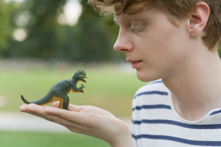 Young man with a toy dinosaur LANG_EVOIMAGES