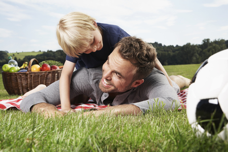 Germany,Cologne,Father and son playing around on picnic blanket