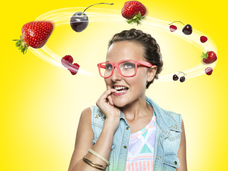 Young woman looking at flying fruit,Composite