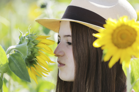 Germany,Cologne,young woman with hat and sunflower