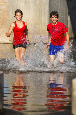 Germany,Baden-Wuerttemberg,Winterbach,athletic young man and young woman running through Rems river LANG_EVOIMAGES