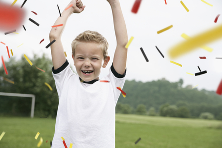 Boy in soccer jersey cheering on soccer pitch LANG_EVOIMAGES