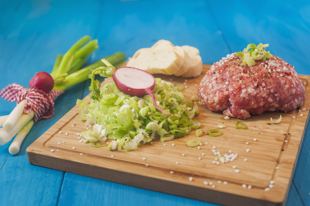 Raw minced meat with spring onions and bread on chopping board,studio shot