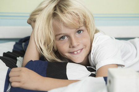 Smiling blond boy lying in bed,portrait LANG_EVOIMAGES