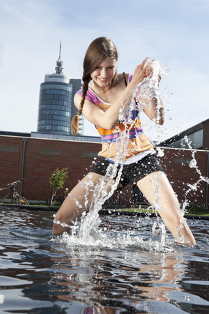Germany,Bavaria,Munich,Young woman splashing with water at fountain