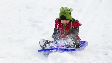Germany,Bavaria,smiling little boy sledging down a hill LANG_EVOIMAGES