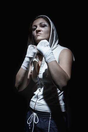 Portrait of a young female boxer holding fists up