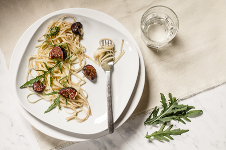 Plate with fig tagliatelle,rocket leaves,sauce and a glass of water,studio shot