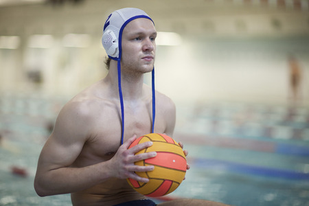 Water polo player outside pool holding ball