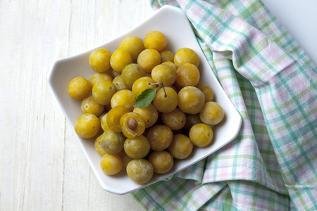 Mirabelles (Prunus domestica subsp. syriaca) in a bowl on wooden table,studio shot LANG_EVOIMAGES