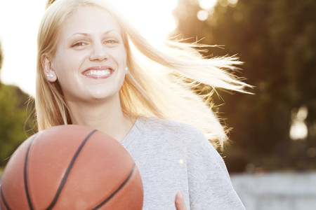 Smiling young woman with basketball