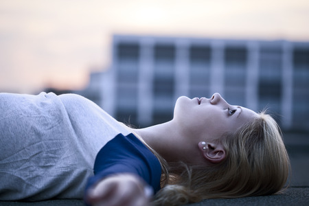 Young woman lying on flat roof LANG_EVOIMAGES