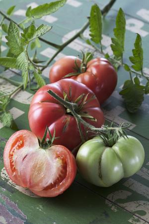 Whole and sliced Silesian raspberry tomatoes (Solanum lycopersicum),studio shot