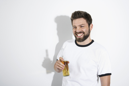 Man in soccer jersey holding beer bottle