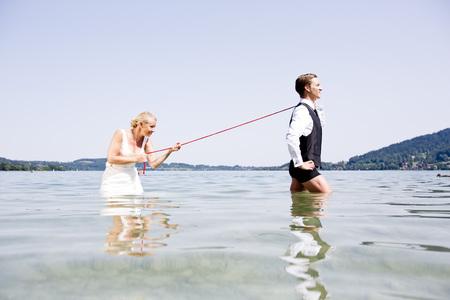 Germany,Bavaria,Tegernsee,Wedding couple standing in lake,bride holding groom on leash