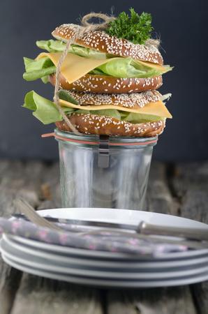 Two sesame bagels with Gouda and lettuce leaf,studio shot