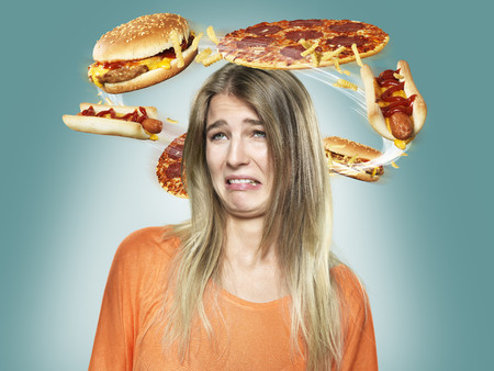 Disgusted young woman with flying fast food around her head,Composite