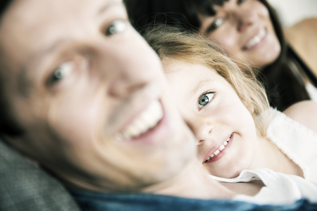 Smiling young parents with little daughter sitting on sofa at home,close-up LANG_EVOIMAGES