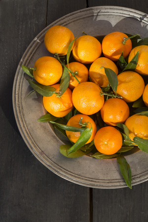 Tangerines in bowl on wooden table