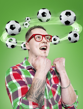 Young man with flying footballs around his head,Composite