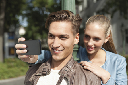 Young couple taking a picture of themselves with a smart phone LANG_EVOIMAGES