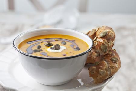 Pumpkin soup in old bowl garnished with pumpkin seed oil,pumpkin seeds and sour cream served with pretzel roll,studio shot LANG_EVOIMAGES