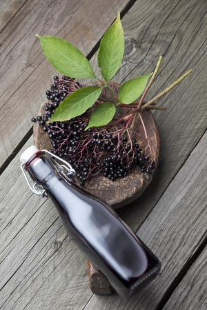 Elderberries (Sambucus),leaves on a wooden shovel and a bottle of elderberry juice on white wooden table,studio shot LANG_EVOIMAGES
