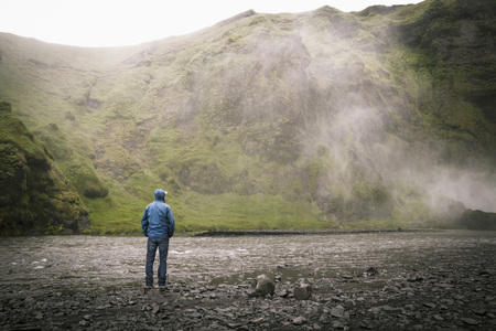 Iceland,Tourist at Skogafoss Waterfall LANG_EVOIMAGES
