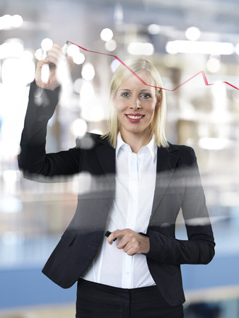 Portrait of business woman drawing red line on glass panel