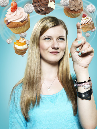 Teenage girl with flying cupcakes around her head,Composite