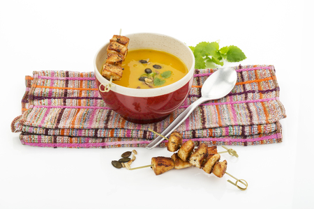 Creamed pumpkin soup in bowl with chicken skewer