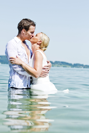 Germany,Bavaria,Tegernsee,Wedding couple standing in lake,kissing LANG_EVOIMAGES