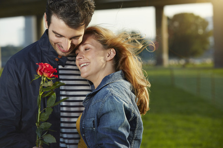 Germany,Dusseldorf,Young couple with red rose LANG_EVOIMAGES