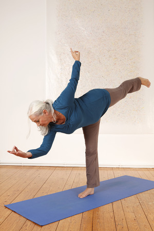 Germany,Dusseldorf,Senior woman practicing yoga