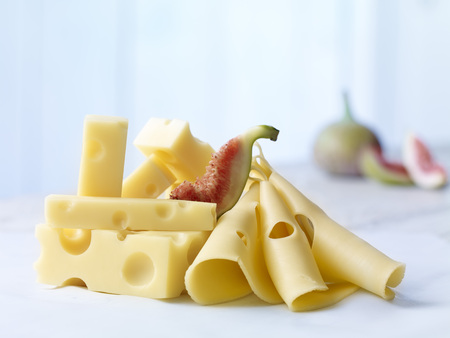 Stack of Emmentaler cheese with slices of fig on wooden table