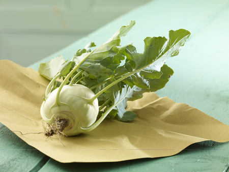 Turnip cabbage (Brassica oleracea) with leaves on wooden table