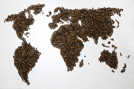 World map shaped of coffee beans on white table