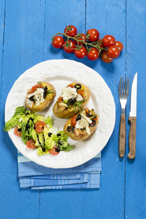 Mediterranean baked potatoes with tomatoes,spring onions,olives,chicken,ricotta and parmesan cheese